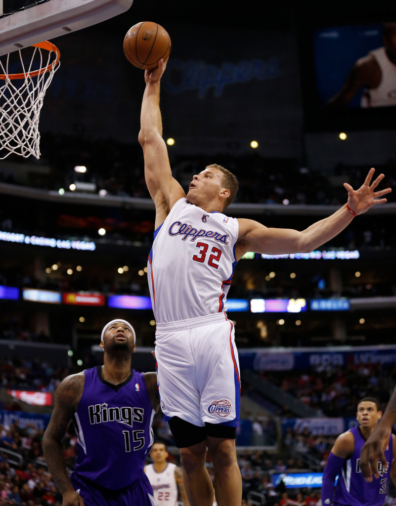 . Los Angeles Clippers forward Blake Griffin dunks the ball over Sacramento Kings center DeMarcus Cousins during the first half of an NBA basketball game in Los Angeles, Sunday, April 12, 2014. (AP Photo/Danny Moloshok)