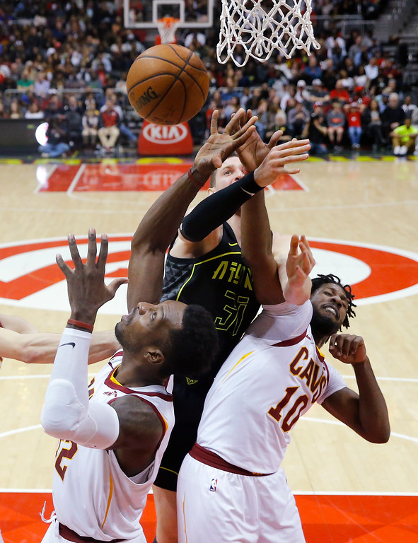 . Cleveland Cavaliers\' John Holland (10) and Jeff Green, left, battle Atlanta Hawks forward Mike Muscala (31) for a rebound during the second half of an NBA basketball game Friday, Feb. 9, 2018, in Atlanta. Cleveland won 123-107. (AP Photo/John Bazemore)