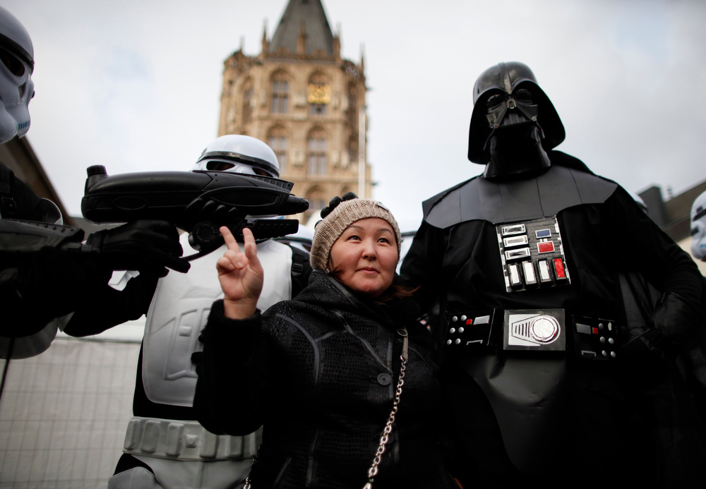 """Description of . A woman poses with a reveller dressed as Darth Vader on \""""Weiberfastnacht\"""" (Women\'s Carnival) in Cologne February 7, 2013. Women\'s Carnival marks the start of a week of street festivals, the highlight of the event being \""""Rosenmontag\"""" (Rose Monday), the final day of the carnival where mass processions are held. REUTERS/Ina Fassbender"""
