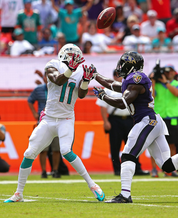 . Mike Wallace #11 of the Miami Dolphins makes a catch against Matt Elam #26 of the Baltimore Ravens during a game  at Sun Life Stadium on October 6, 2013 in Miami Gardens, Florida.  (Photo by Mike Ehrmann/Getty Images)