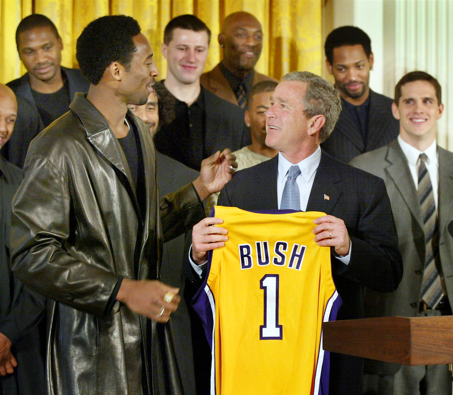 . President Bush holds up a Los Angeles Lakers jersey that was given to him by Lakers guard Kobe Bryant, left, during a ceremony for the 2001 NBA World Champions, rear, in the East Room of the White House Monday, Jan. 28, 2002. (AP Photo/Doug Mills)