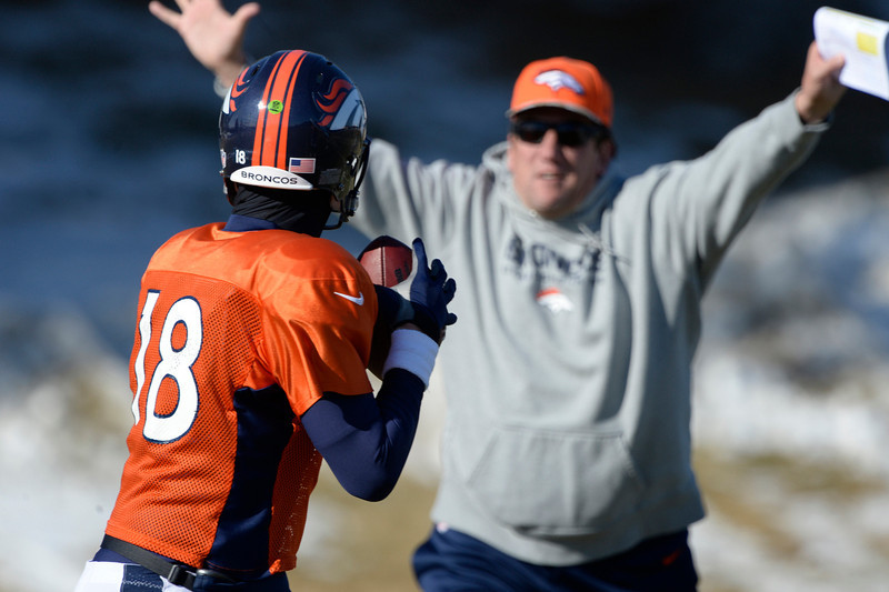 . Denver Broncos quarterback Peyton Manning (18) runs through drills as Gregg Knapp tries to distract him during his throwing motion at practice January 8, 2014 at Dove Valley. The Denver Broncos are preparing for their Divisional Game against the San Diego Chargers at Sports Authority Field. (Photo by John Leyba/The Denver Post)