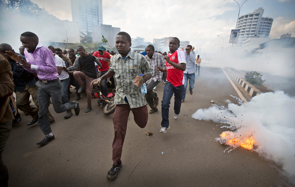 . Opposition supporters, some carrying rocks, flee from exploding tear gas grenades fired by riot police, during a protest in downtown Nairobi, Kenya Monday, May 16, 2016. Kenyan police have tear-gassed and beaten opposition supporters during a protest demanding the disbandment of the electoral authority over alleged bias and corruption. (AP Photo/Ben Curtis)