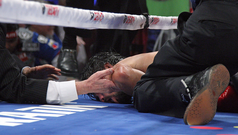. Hands reach in ringside to support the head of Manny Pacquiao after he was knocked out by Juan Manuel Marquez on December 8, 2012, at the MGM Grand Garden in Las Vegas, Nevada. JOHN GURZINSKI/AFP/Getty Images