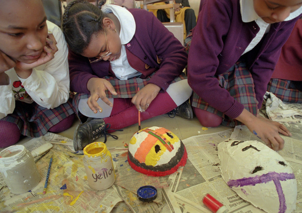 Description of . Larae Lindsay, 10, center, helps Tiffany Morgan, 11, left, paint her African mask during a fifth grade class project at St. Charles Borromeo school in the Harlem section of New York, Thursday, Feb. 1, 1996. Students of the school plastered, molded, and painted death and dance masks to celebrate the first day of black history month. (AP Photo/Wally Santana)