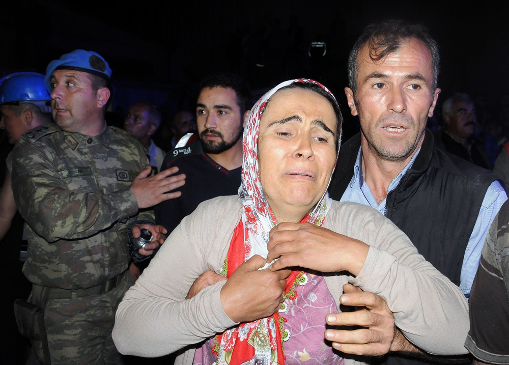 . Family members gather near the mine after an explosion and fire at a coal mine killed at least 17 miners and left up to 300 workers trapped underground, in Soma, in western Turkey, Tuesday, May 13, 2014, a Turkish official said. Twenty people were rescued from the mine but one later died in the hospital, Soma administrator Mehmet Bahattin Atci told reporters. The town is 250 kilometers (155 miles) south of Istanbul. The death toll was expected to rise.(AP Photo/Depo Photos)