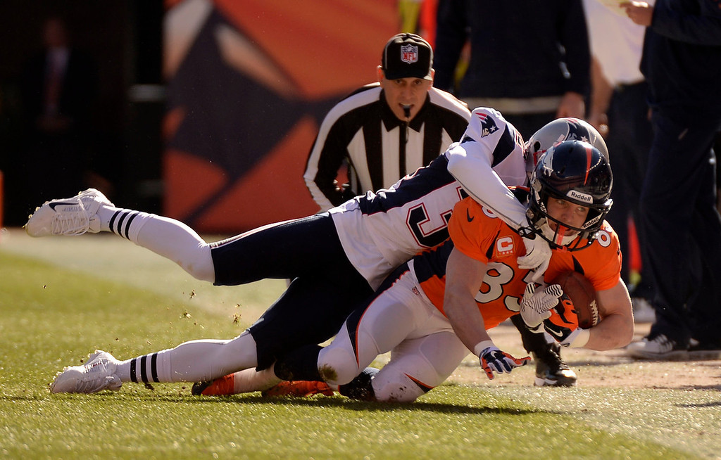 . Denver Broncos wide receiver Wes Welker (83) makes a catch during the first quarter and taken down by New England Patriots free safety Devin McCourty (32), The Denver Broncos vs. The New England Patriots in an AFC Championship game  at Sports Authority Field at Mile High in Denver on January 19, 2014. (Photo by John Leyba/The Denver Post)