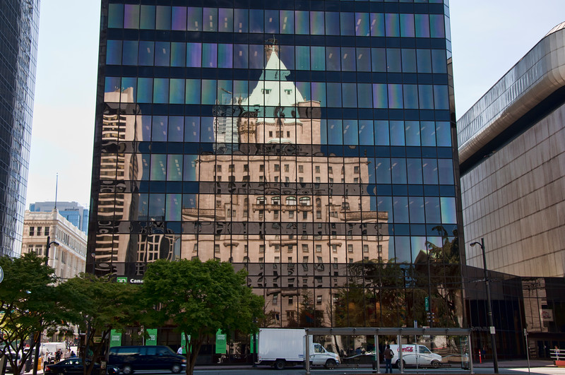 A modern building reflects the Fairmont hotel in downtown Vancouver.