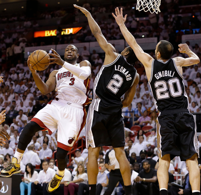 . The Miami Heat\'s Dwyane Wade (3) takes the ball to the hoop as San Antonio Spurs\' Kawhi Leonard (2) and Manu Ginobili (20) defend during the second half in Game 7 of the NBA basketball championships, Thursday, June 20, 2013, in Miami. (AP Photo/Lynne Sladky)