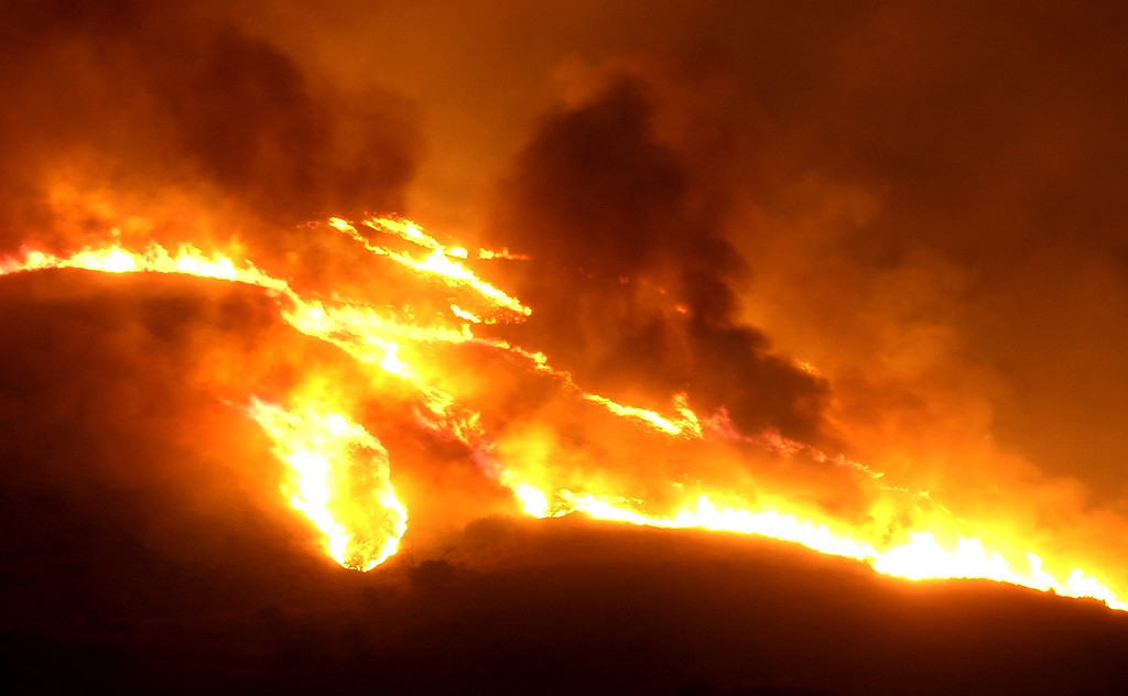 . Flames burn in the mountains above Hopper Canyon in Fillmore in Southern California\'s Ventura County after sunset Sunday, Oct. 26, 2003.  The fire known as the Piru fire, that had been approcaching containment, flared anew Sunday.  (AP Photo/Reed Saxon)