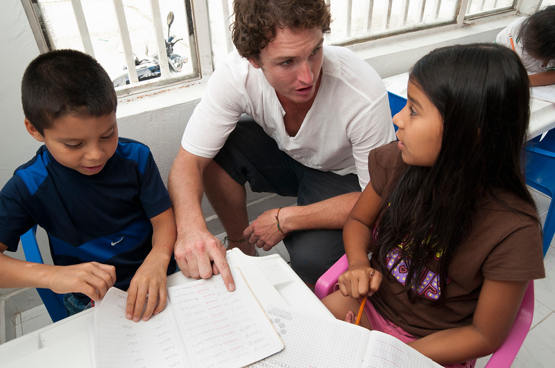 Volunteer helps children with their school homework.