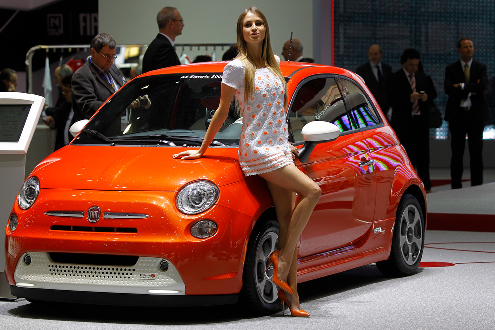 . A hostess poses in front of a Fiat 500 during the first media day of the 83rd Geneva International Motor Show, Switzerland, Tuesday, March 5, 2013. The Motor Show will open its gates to the public from March 7 to 17.  (AP Photo/Laurent Cipriani)