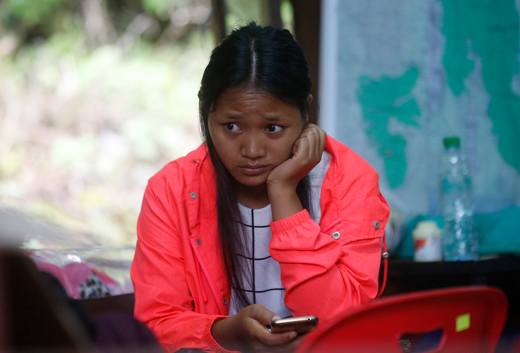 . A family member sits in tent near a cave where 12 boys and their soccer coach have been trapped since June 23, in Mae Sai, Chiang Rai province, in northern Thailand Saturday, July 7, 2018. The soccer coach trapped in a cave with 12 Thai boys apologized to their parents in the first letter he and the team have sent out through divers, in which the boys say they\'re doing well and missing their families. (AP Photo/Sakchai Lalit)