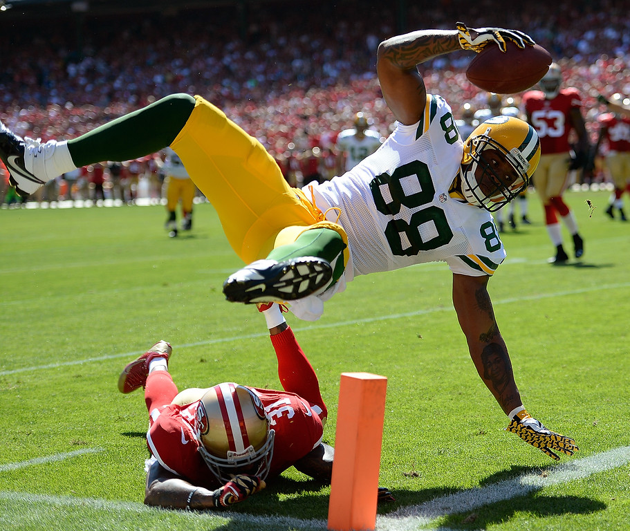 . Jermichael Finley #88 of the Green Bay Packers scores on a twelve yard pass play diving over the tackle of Donte Whitner #31 of the  San Francisco 49ers during the second quarter at Candlestick Park on September 8, 2013 in San Francisco, California.  (Photo by Thearon W. Henderson/Getty Images)