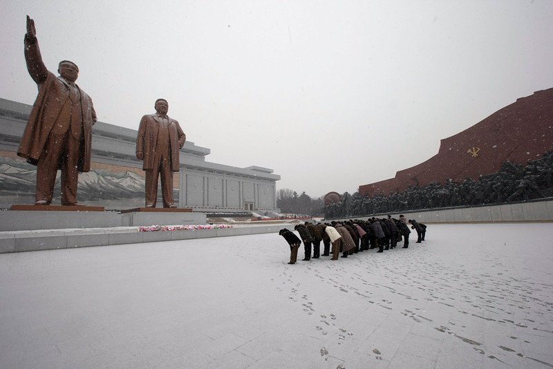 . North Koreans bow in front of the statues of late North Korean leaders Kim Il Sung, left, and Kim Jong Il at Mansu Hill as it snows in Pyongyang, North Korea, Friday, Dec. 21, 2012. (AP Photo/Ng Han Guan)