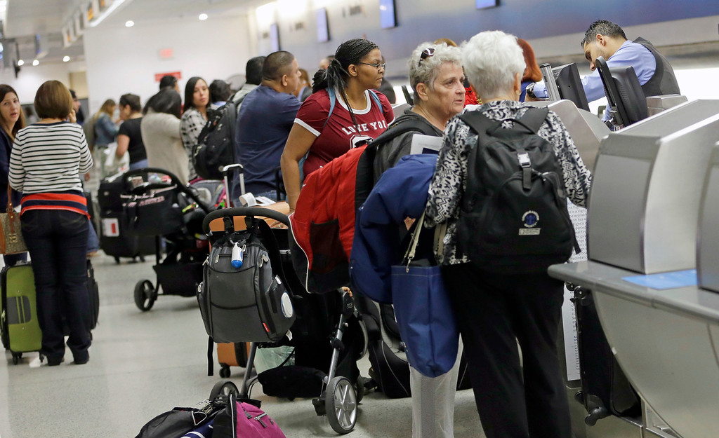 . Passengers check in their luggage at the counter at Miami International Airport, Wednesday, Nov. 23, 2016, in Miami. Almost 49 million people are expected to travel 50 miles or more for the Thanksgiving holiday, the most since 2007, according to AAA.  (AP Photo/Alan Diaz)