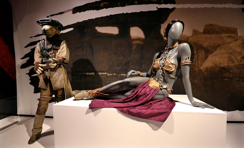 . In this photo taken Thursday, Jan. 29, 2015, Princess Leia\'s slave bikini, right, and her Boushh disguise are displayed as part of an exhibit on the costumes of Star Wars at Seattle�s EMP Museum. The creators of the new exhibit, with 60 original costumes from the six Star Wars movies, are hoping to gather geeks, fashionistas and movie fans together to discuss how clothing helps set the scene. The exhibit, �Rebel, Jedi, Princess, Queen: Star Wars and the Power of Costume,� will be in Seattle through early October and then travel across the United States through 2020. (AP Photo/Elaine Thompson)