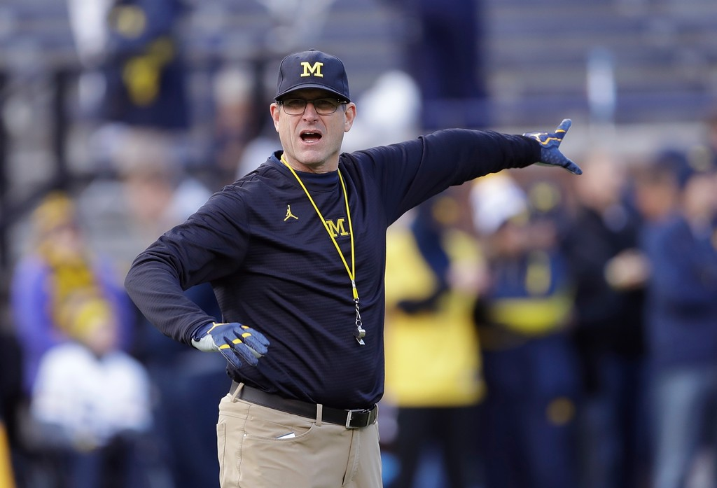 . Michigan head coach Jim Harbaugh gestures to his team during warmups before an NCAA college football game against Ohio State, Saturday, Nov. 25, 2017, in Ann Arbor, Mich. (AP Photo/Carlos Osorio)