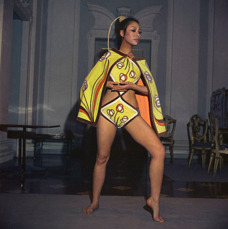 . A bikini of green and brown terry cloth, with a matching bikini-cover-up-cape made of two terry cloth bath towels, that can be worn on the shoulders or covering front and back. by Emilio Pucci of Florence, model is Mei-Ling-Chan of Hong Kong fashions Italian swim suit in 1967. (AP Photo/Mario Torrisi)