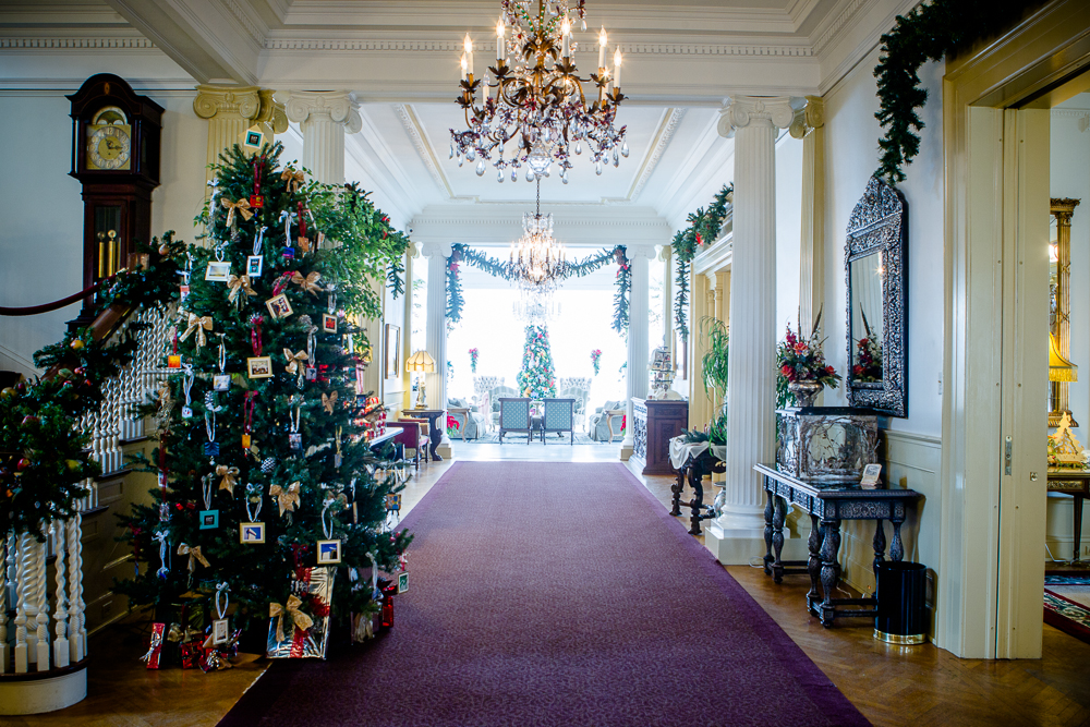 . A long hallway at the Governor\'s Mansion shows off garlands, antique furnishings and a tree at left decorated with miniature versions of Colorado artists\' works. Photo by Mark Broste