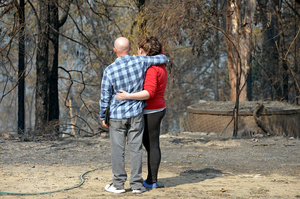 """. Amy Hubbard (R) and her father Darren inspect their house destroyed by bush fires in Winmalee in Sydney\'s Blue Mountains on October 18, 2013. Residents faced scenes of devastation on October 18 after bush fires ravaged communities and destroyed \""""hundreds\"""" of homes in southeastern Australia with dozens of blazes still burning out of control. AFP PHOTO / Greg  WOOD/AFP/Getty Images"""