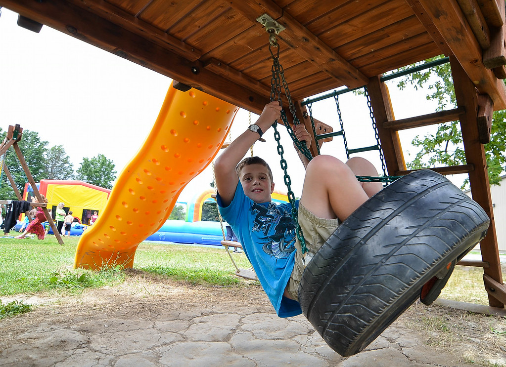 . Eric Bonzar/EBonzar@morningjournal.com<p> Zack Strother, 11, swings on a tire swing while attending the Camp I.D.E.A.S. carnival July 16.