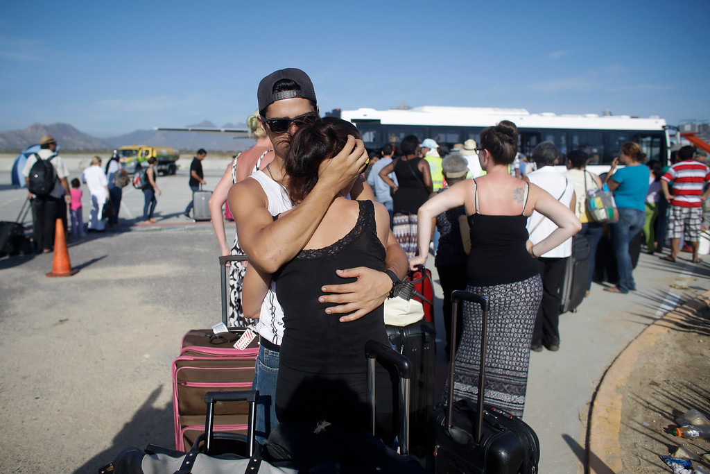 . Jesus Guerrero, 24, of Mexico, hugs his girlfriend Ditte Smedegaard, of Denmark, as they wait in line to be evacuated out of Los Cabos, Mexico, Thursday, Sept. 18, 2014. Mexican authorities said 8,000 people, including tourists and locals anxious to leave, would be airlifted out on Thursday from Los Cabos following the blow from Hurricane Odile. (AP Photo/Victor R. Caivano)