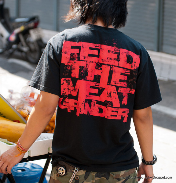 "Man with a t-shirt that says ""Feed the meat grinder"" in Silom, Bangkok, in December 2009"