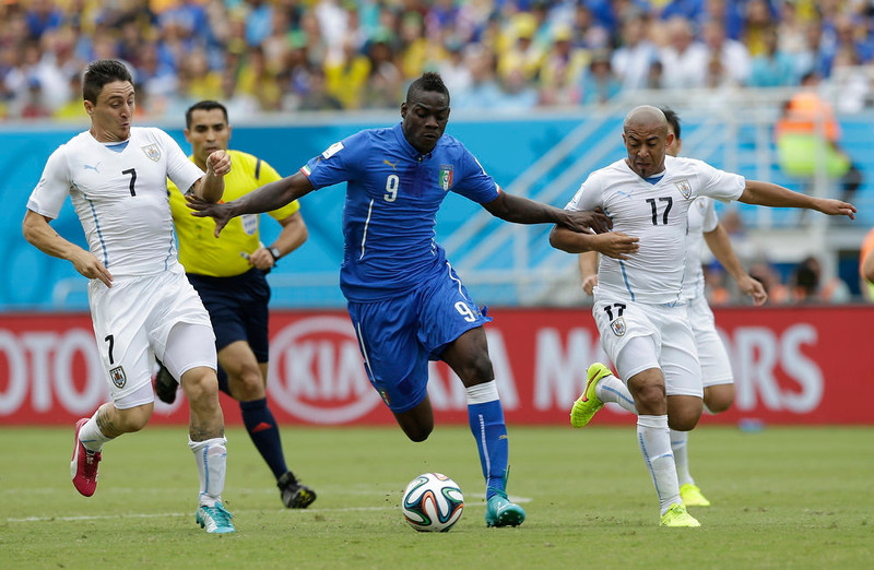 . Italy\'s Mario Balotelli pushes off Uruguay\'s Cristian Rodriguez (7) and Egidio Arevalo Rios during the group D World Cup soccer match between Italy and Uruguay at the Arena das Dunas in Natal, Brazil, Tuesday, June 24, 2014. (AP Photo/Ricardo Mazalan)