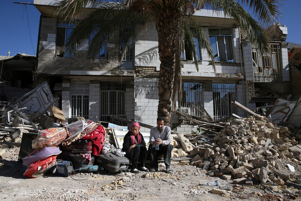 . Survivors sit in front of a destroyed house on the earthquake site in Sarpol-e-Zahab in western Iran, Tuesday, Nov. 14, 2017. Rescuers are digging through the debris of buildings felled by the Sunday earthquake in the border region of Iran and Iraq. (AP Photo/Vahid Salemi)