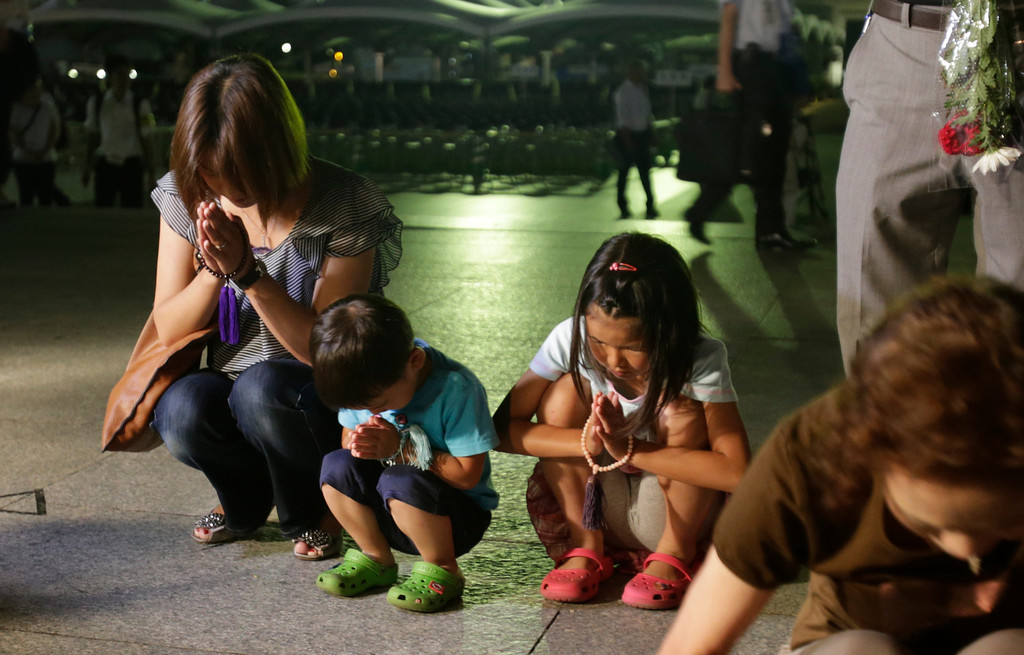 . People pray for the atomic bomb victims at the Hiroshima Peace Memorial Park in Hiroshima, western Japan, early Tuesday, Aug. 6, 2013. Japan marked the 68th anniversary Tuesday of the atomic bombing of Hiroshima with pledges to seek to eliminate nuclear weapons. (AP Photo/Shizuo Kambayashi)