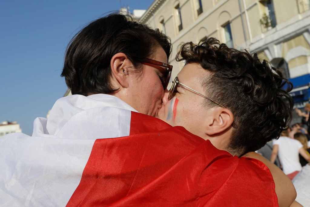 . A couple exchange a kiss while celebrating France\'s World Cup victory over Croatia in Marseille, southern France, Sunday, July 15, 2018. (AP Photo/Claude Paris)