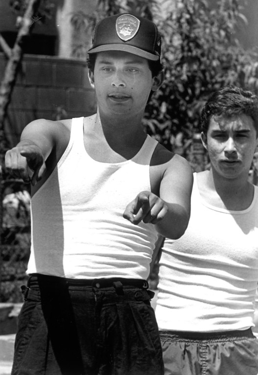. Jaime Burgoin, left, and his brother Julio, sat on Richard Ramirez, the Night Stalker suspect, while neighbors compared Ramirez\'s face with newspaper pcitures.  (Daily News file photo)