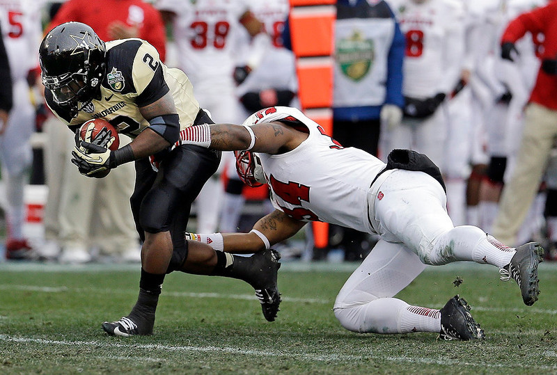 . Vanderbilt running back Zac Stacy (2) is stopped by North Carolina State linebacker Rickey Dowdy (34) in the first quarter of the Music City Bowl NCAA college football game on Monday, Dec. 31, 2012, in Nashville, Tenn. (AP Photo/Mark Humphrey)