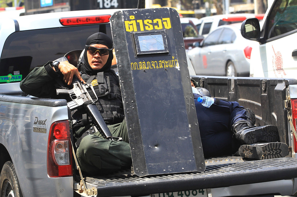 . Riot police officers  hold protective shields on a pickup truck  after clashes in Bangkok, Thailand, Tuesday, Feb. 18, 2014. (AP Photo/Sakchai Lalit)