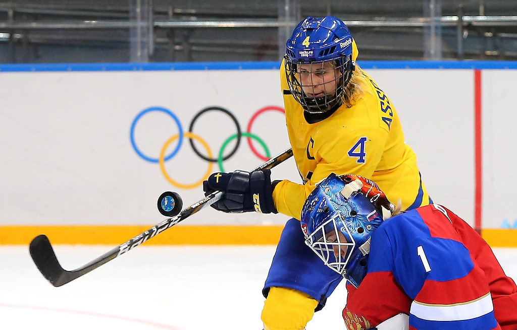 . Jenni Asserholt #4 of Sweden tries to knock a puck out of the air against Anna Prugova #1 of Russia in the third period during the Women\'s Ice Hockey Preliminary Round Group B game on day six of the Sochi 2014 Winter Olympics at Shayba Arena on February 13, 2014 in Sochi, Russia.  (Photo by Martin Rose/Getty Images)