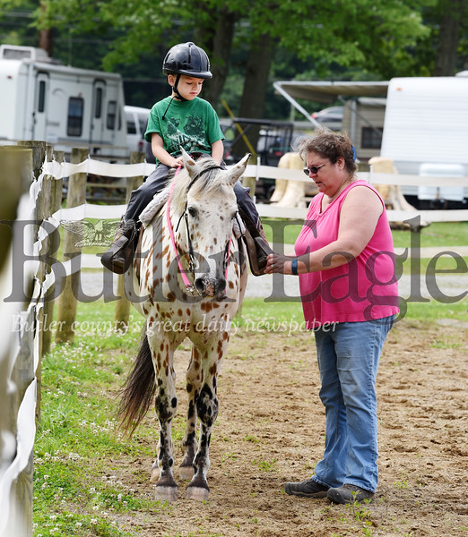 Harold Aughton/Butler Eagle: Toni Lukavich of North Washington fixes the stirrup for her grandson, six-year-old, Ryder Snow of Boyers at the Butler Fair, Saturday, June 29.  Ryder is preparing for the pleasure riding and gaming competition on his horse, Frosty, a 37-year-old Colorado Rangerbred. This is Frosty's 18th year of competition at the Butler Fair.