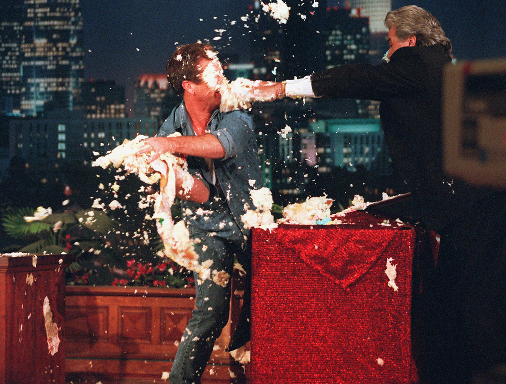 """. Jay Leno, host of \""""The Tonight Show,\"""" right, is hit with his anniversary cake by actor/director Mel Gibson, left, during his fifth year anniversary show at the Burbank, Calif., studio Thursday, May 22, 1997. Leno is celebrating his fifth year as host of \""""The Tonight Show,\"""" succeeding Johnny Carson. (AP Photo/Damian Dovarganes)"""