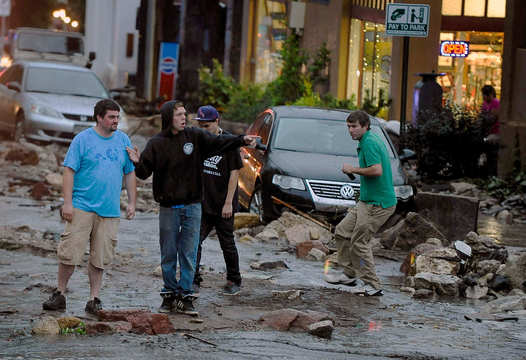 . People look in disbelief as they see the damage on Park Avenue after a flash flood ripped through downtown, Friday, Aug. 9, 2013 in Manitou, Colo. A mudslide has closed U.S. 24 between Cascade and Manitou Springs, and flash flooding in Manitou Springs is stranding vehicles in high, fast-moving water. (AP Photo/The Colorado Springs Gazette, Michael Ciaglo)