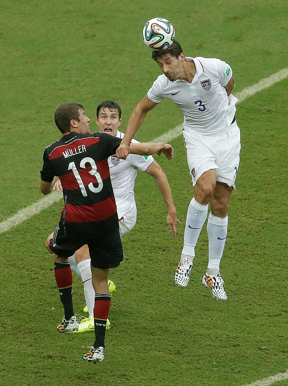 . United States\' Omar Gonzalez beds the ball over Germany\'s Thomas Mueller during the group G World Cup soccer match between the USA and Germany at the Arena Pernambuco in Recife, Brazil, Thursday, June 26, 2014. (AP Photo/Hassan Ammar)