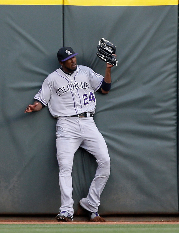 . Colorado Rockies center fielder Dexter Fowler catches a long fly ball hit by Cincinnati Reds\' Jay Bruce in the fifth inning of a baseball game, Tuesday, June 4, 2013, in Cincinnati. (AP Photo/Al Behrman)