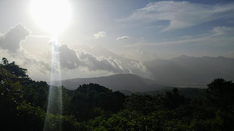 sun in the sky over mountainous landscape