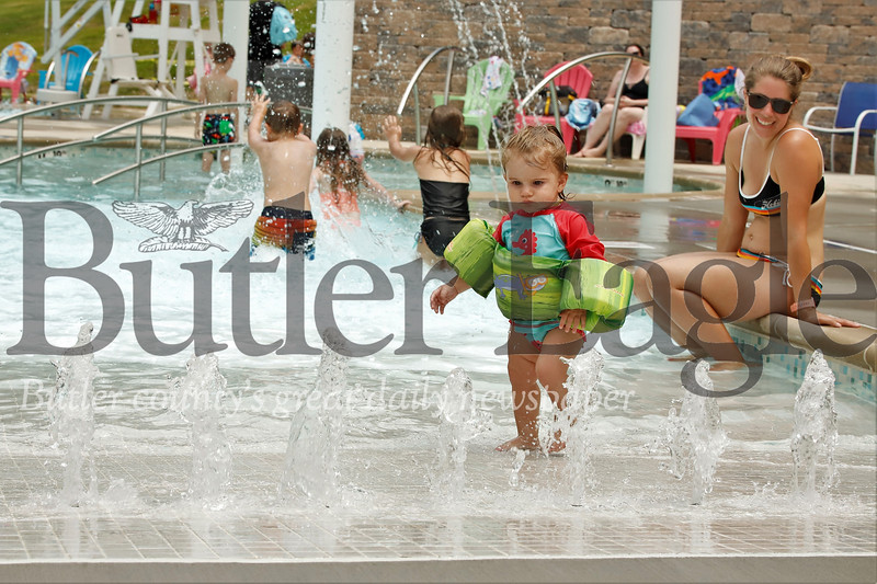 Floatied up and ready to explore the new kiddie pool, Selah Shriver of Zelienople contemplates her next move, while her mom, Heather, looks on. Seb Foltz/Butler Eagle