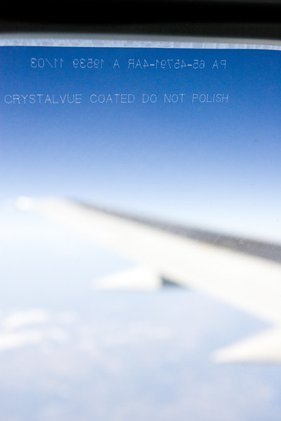 """The sign """"Crystalvue coated do not polish"""" on an airplane window."""