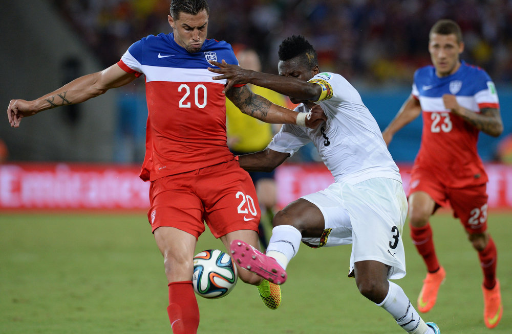 Description of . Ghana's forward Asamoah Gyan(R) vies with US defender Geoff Cameron (L) during a Group G football match between Ghana and US at the Dunas Arena in Natal during the 2014 FIFA World Cup on June 16, 2014.  AFP PHOTO / CARL DE SOUZACARL DE SOUZA/AFP/Getty Images