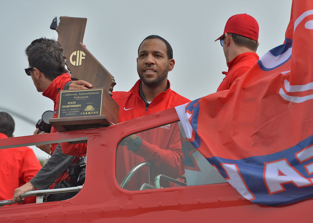 . TBR29-RUHS_PARADE--- Redondo Beach, CALIFORNIA--3/28/13--- Staff Photo: Robert Casillas / LANG---  The Redondo Union High basketball team was celebrated Thursday for their CIF State title. The festivities began with a double decker bus ride around the school and a rally at City Hall.  Coach Reggie Morris Jr. holds championship trophy.