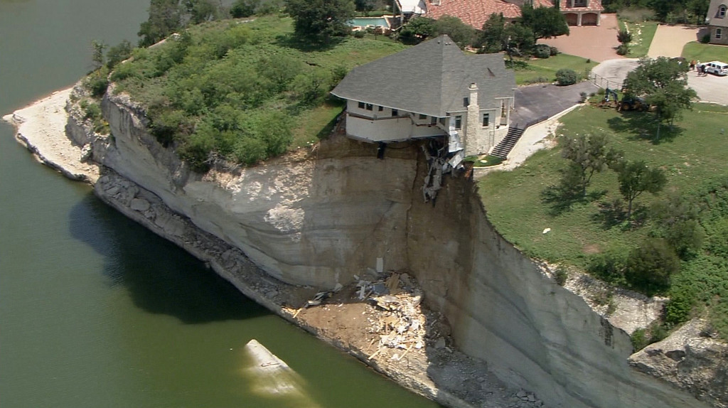 . In this image taken from video provided June 12, 2014, by WFAA.Com, a luxury house teeters on a cliff about 75 feet above Lake Whitney in Whitney, Texas. The owner of a vacant luxury house teetering on a crumbling 75-foot cliff over a Central Texas lake has decided to burn the house and clear the lot of the debris. (AP Photo/WFAA.Com)