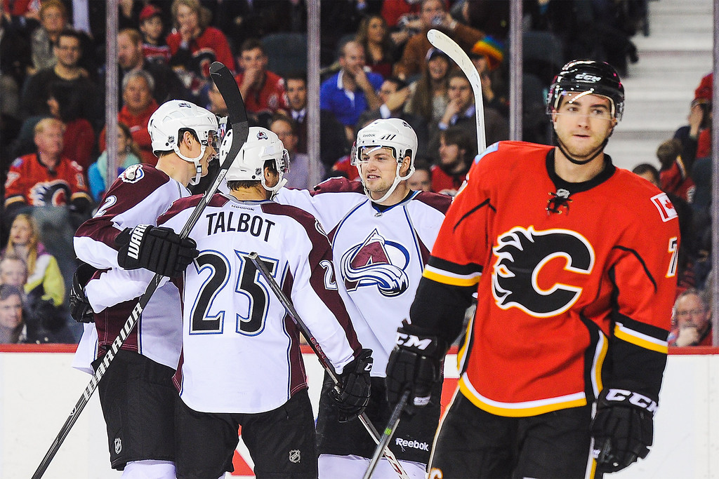 . CALGARY, AB - DECEMBER 6: Maxime Talbot #25 of the Colorado Avalanche celebrates scoring his team\'s first goal against the Calgary Flames while a dejected T.J. Brodie #7  skates away during an NHL game at Scotiabank Saddledome on December 6, 2013 in Calgary, Alberta, Canada. (Photo by Derek Leung/Getty Images)