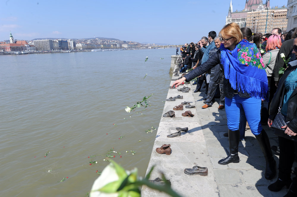 Description of . Hungarian and foreign university students and their teachers from different countries throw flowers into the Danube River in Budapest, nearby the parliament building on April 8, 2013 during their commemoration for the victims of the Holocaust, the genocide that resulted in the annihilation of 6 million Jews, 2 million gypsies (Roma and Sinti) by the Nazi regime and its collaborators.  AFP PHOTO / ATTILA KISBENEDEK