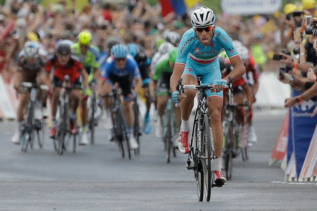 . Italy\'s Vincenzo Nibali grimaces as he strains to stay ahead of the sprinting pack, rear, to win the second stage of the Tour de France cycling race over 201 kilometers (124.9 miles) with start in York and finish in Sheffield, England, Sunday, July 6, 2014. (AP Photo/Laurent Cipriani)